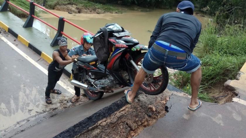 Pengendara saat memaksa melintasi ruas jalan di lokasi jembatan yang ambruk.