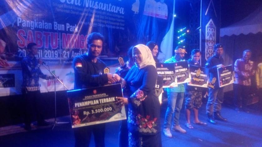 Bupati Kobar Hj Nurhidayah saat menyerahkan secara simbolis hadiah pagi pemenang lomba seni Sabtu (20/4) tadi malam.