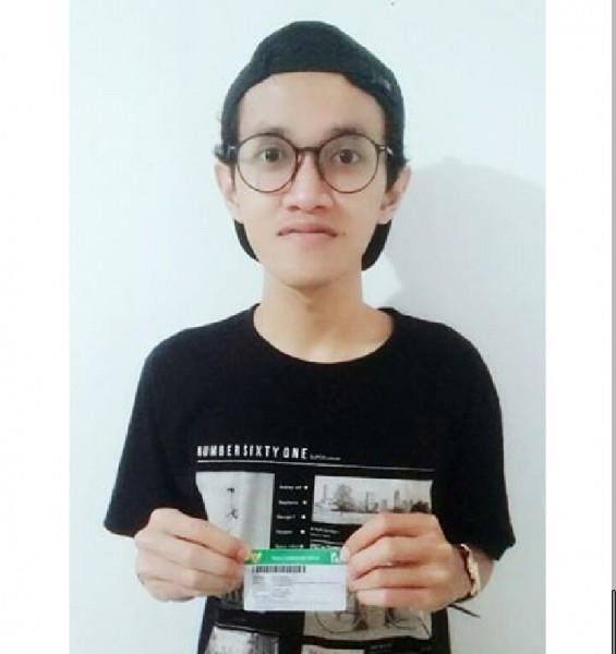 Aziz Wicaksono saat memperlihatkan kartu JKN-KIS miliknya.