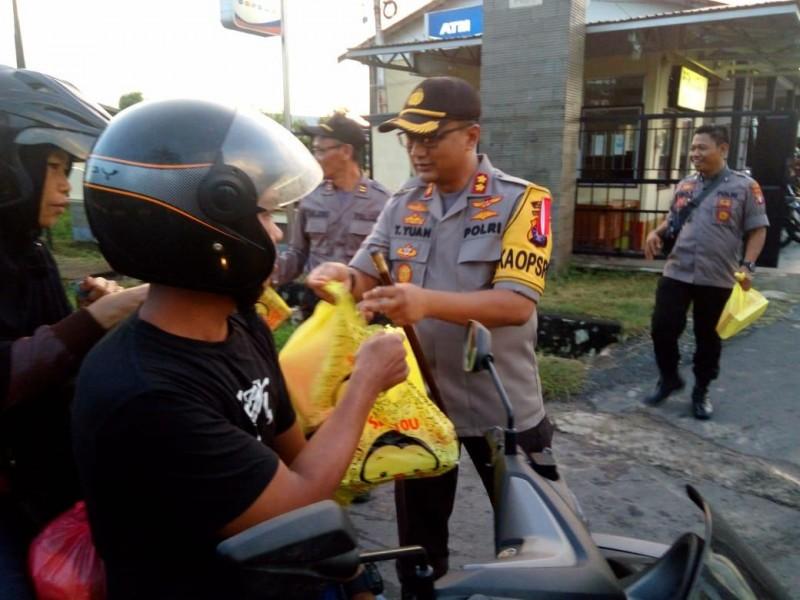 Kapolres Kapuas AKBP Tejo Yuantoro saat membagikan takjil kepada pengendara yang melintas di depan Polres Kapuas Selasa (7/5).