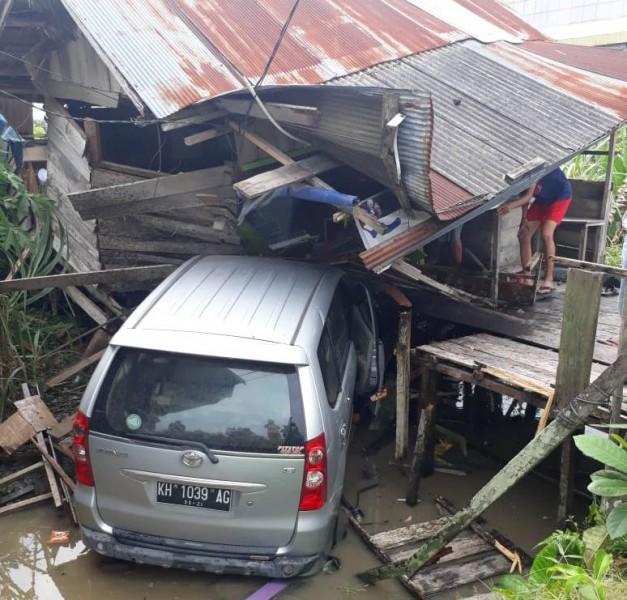 Mobil Avanza saat nyungsep ke parit dan menabrak rumah warga Kelurahan Baru Sabtu (18/5).