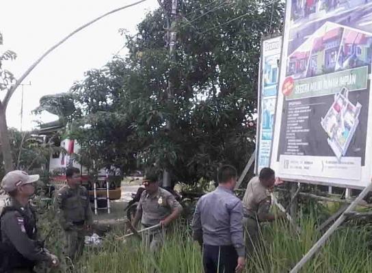 Anggota Satpol PP Katingan saat menertibkan baliho tak berizin yang dipasang di ruas Jalan Tjilik Riwut Kamis (9/5).