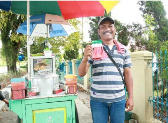 Sunari pedagang bakso keliling di Kota Palangka Raya saat memperlihatkan kartu JKN-KIS atau biasa disebut Kartu BPJS Kesehatan yang ia miliki belum lama ini.
