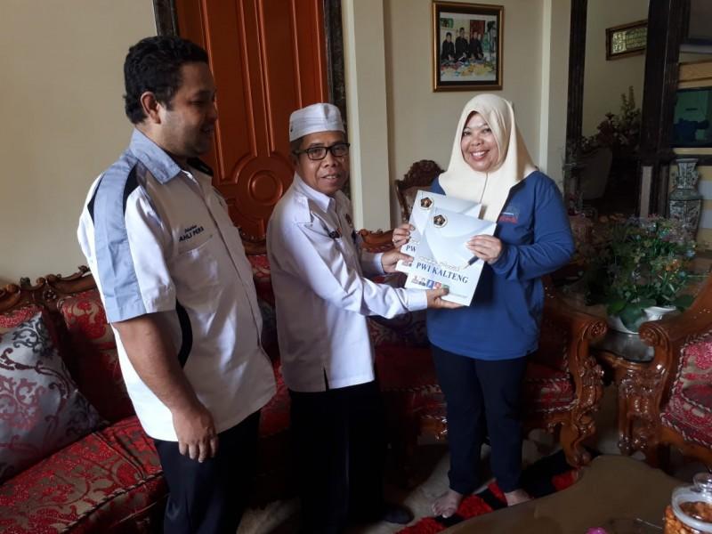 Ketua PWI Kalteng Sutransyah saat menyerahkan buku putih kepada Bupati Kobar Hj Nurhidayah dikediamanya.