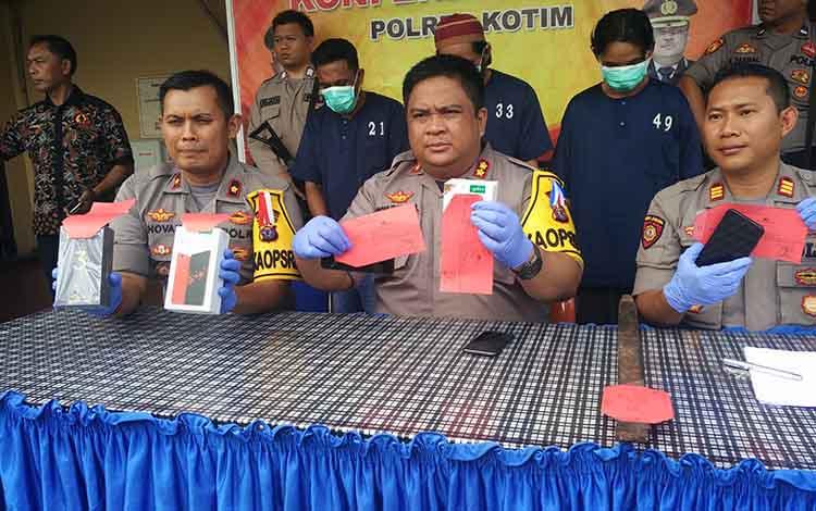 Kapolres Kotim AKBP M Rommel saat memperlihatkan barbuk ponsel yang sempat dicuri pelaku ketika press release di Mapolres Kotim Jumat (14/6/2019).