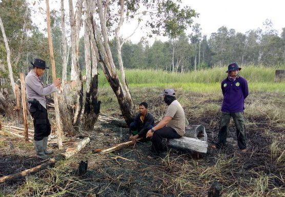 Anggota Polsek Sebangau saat mengamankan pelaku di lokasi kejadian kebakaran, Sabtu (27/7/2019).