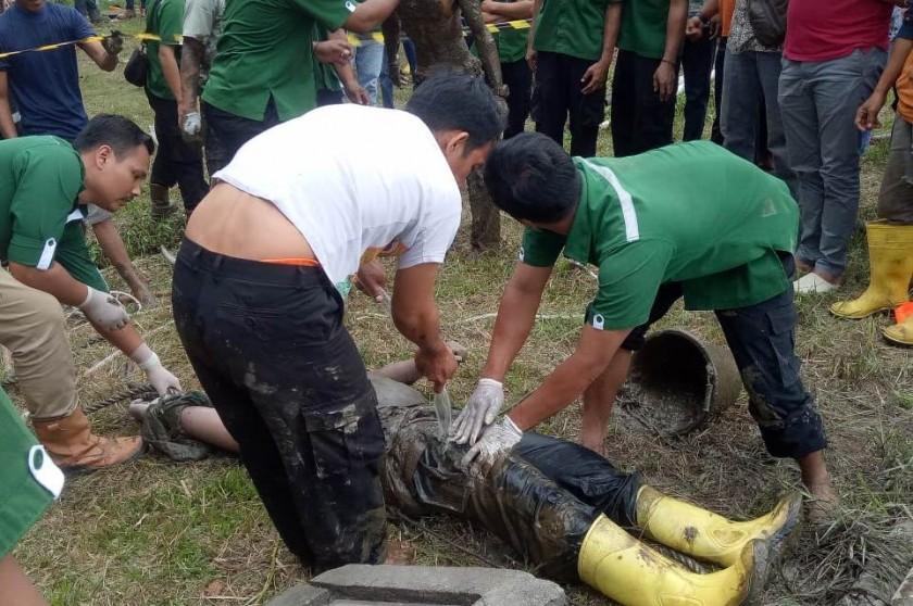 Rekan kerja korban saat mengevakuasi jasad korban dari dalam kolam, Jumat (12/7/2019).