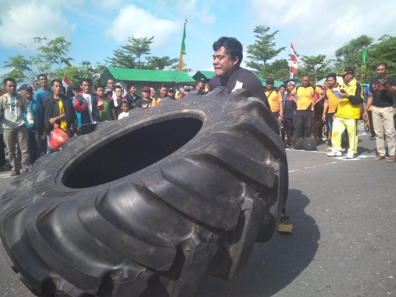 Salah seorang peserta saat mengikuti kegiatan mengangkat ban besar, Minggu (14/7/2019).
