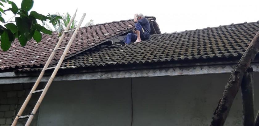 Kakek Slamet saat naik ke atas atap rumahnya Minggu (21/7/2019).