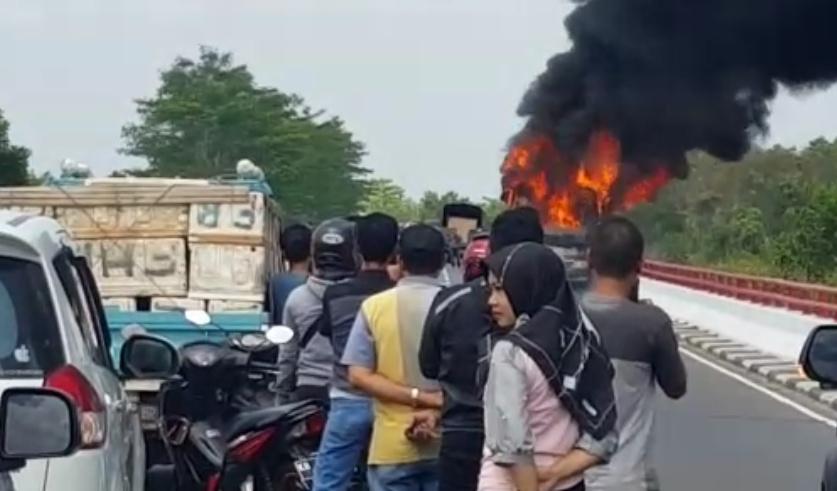 Warga pengendara saat menyaksikan peristiwa terbakarnya bus Polres Kapuas di Jembatan Tumbang Nusa Rabu (31/7/2019).