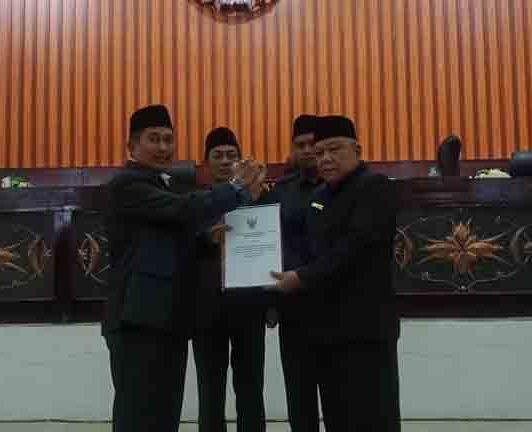 Ketua DPRD Mura Gad F Silam saat melakukan serah terima dengan Wabup Mura Rejikinoor saat digelarnya rapat paripurna Rabu (3/7/2019).