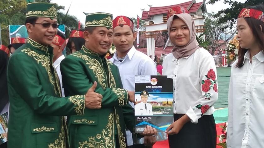 Bupati Mura Perdie M Yosep dan Wabup Rejikinoor saat menyerahkan buku kepada pelajar, saat acara HUT Mura Kamis (1/8/2019).