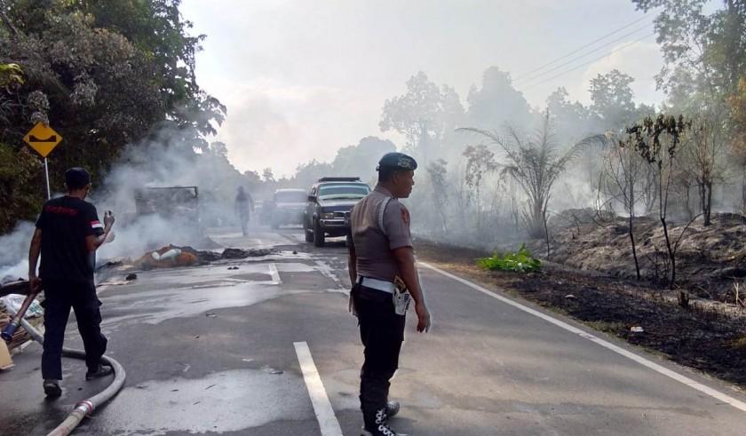 Petugas kepolisian saat mengatur arus lalu lintas seusai kejadian kebakaran mobil bermuatan kardus bekas di ruas Jalan Trans Kalimantan Senin (5/8/2019).