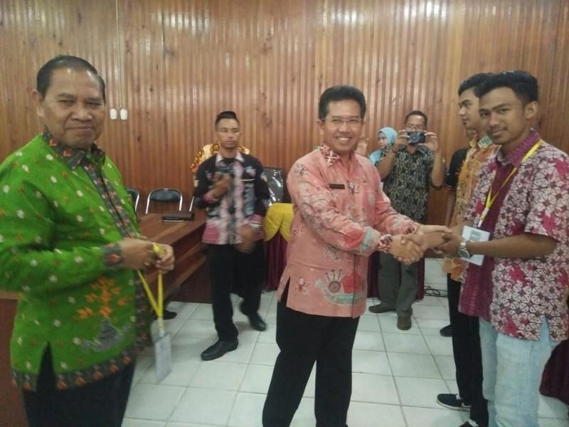 Kepala Disnakertran Provinsi Kalteng Syahril Tarigan didampingi Kepala Disnakertran Kobar Gst Nur Aini saat secara simbolis memberikan tanda peserta Jumat (23/8/2019).