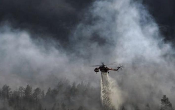 Helikopter saat melakukan pemadaman api dari udara di kawasan TNTP yang terbakar Jumat (24/8/2019).