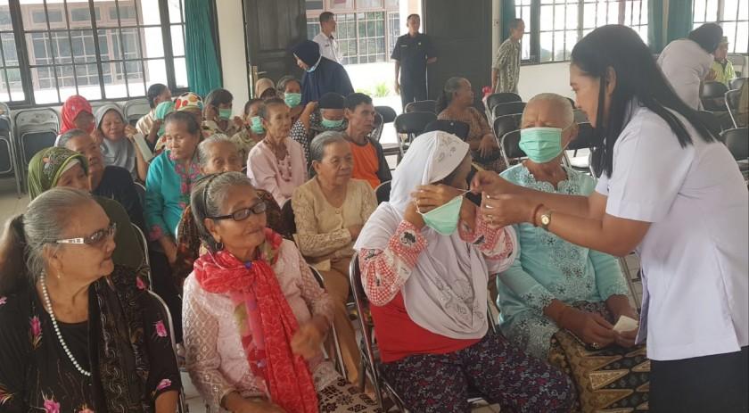 Petugas DP3APPKB Kalteng saat memasangkan masker yang dibagikan kepada para lansia.
