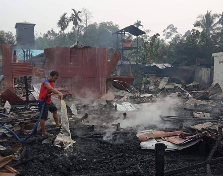 Warga saat memadamkan sisa puing api yang masih menyala di lokasi kejadian Minggu (15/9/2019).