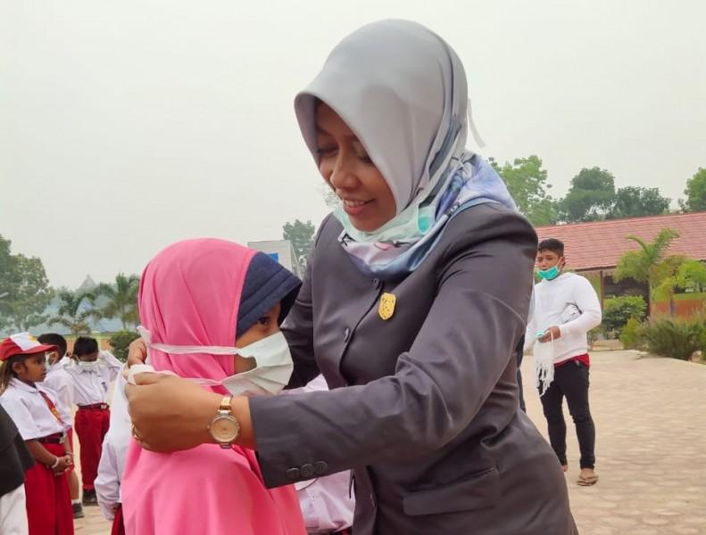 Anggota DPRD Kobar Sri Lestari saat memasangkan masket kepada muris sekolah dasar saat membagikannya disalah satu sekolah Selasa (17/9/2019).