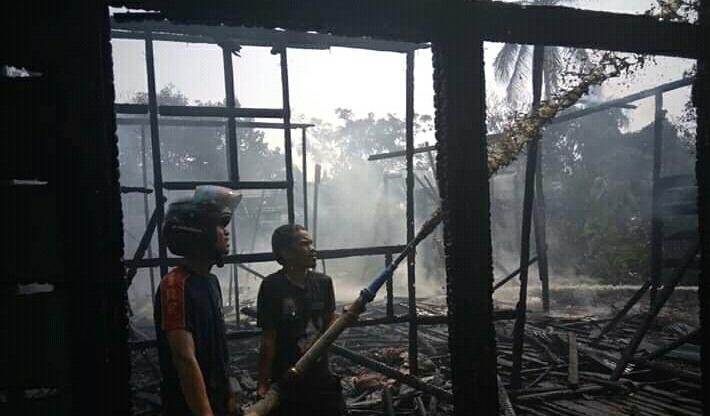 Petugas pemadam kebakaran saat melakukan pemadaman sisa api di puing bangunan Minggu (29/9/2019).