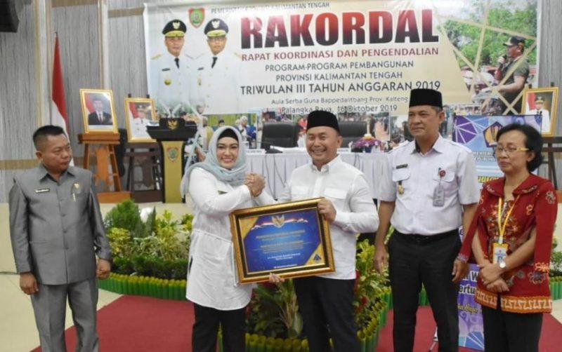 Gubernur Kalteng Sugianto Sabran saat menyerahkan secara simbolis piagam penghargaan kepada Wakil Wali Kota Palangka Raya Umi Mastikah, saat acara Rakordal Rabu (16/10/2019).