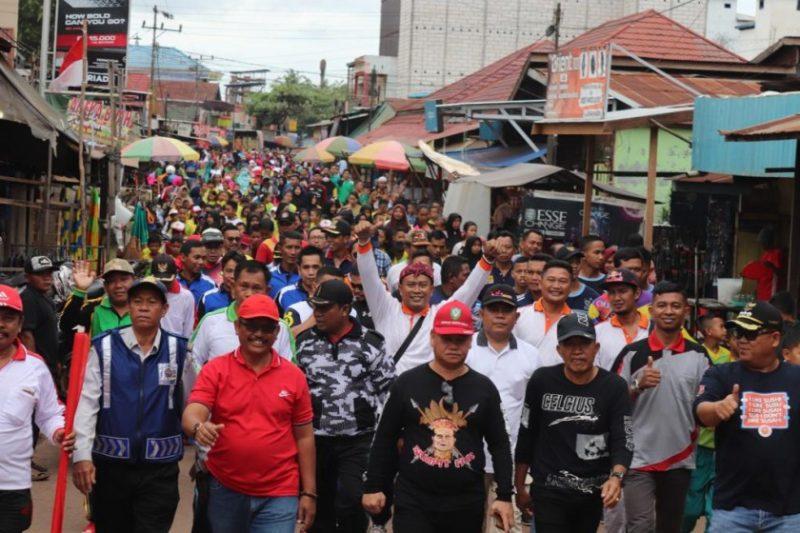 Sekda Kotim Halikinoor (tengah baju hitam pakai topi merah) dan Camat Parenggean Siyono (baju merah) saat mengikuti jalan sehat bersama ribuan warga Kecamatan Parenggean Senin (7/10/2019).