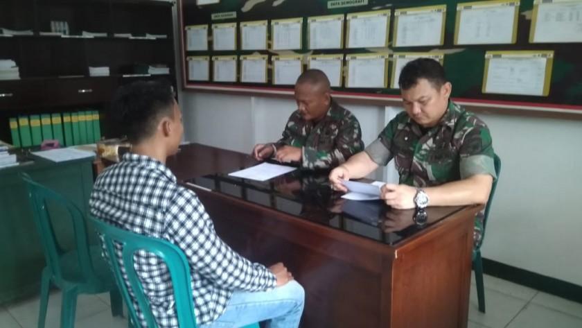Danramil Kumai Kapten Arm Ahmad Zubaidi saat meneliti berkas peserta yang mendaftar.