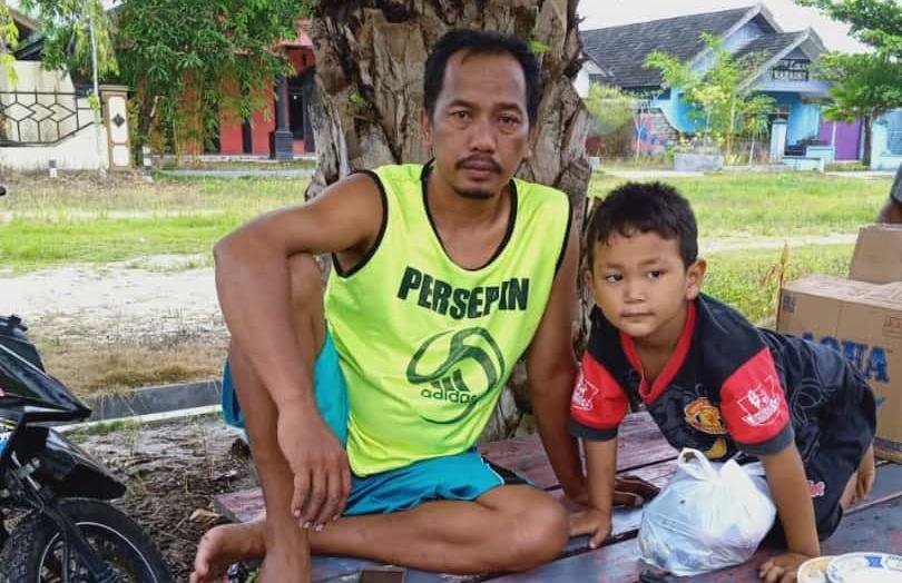 Ketua RT 18 Desa Pasir Panjang Harto bersama anaknya.