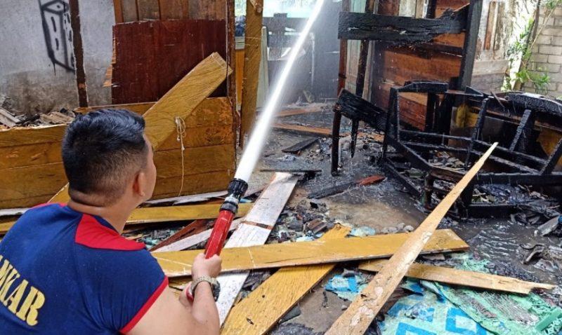 Petugas Damkar Kobar saat memadamkan sisa api di lokasi kejadian Minggu (3/11/2019).