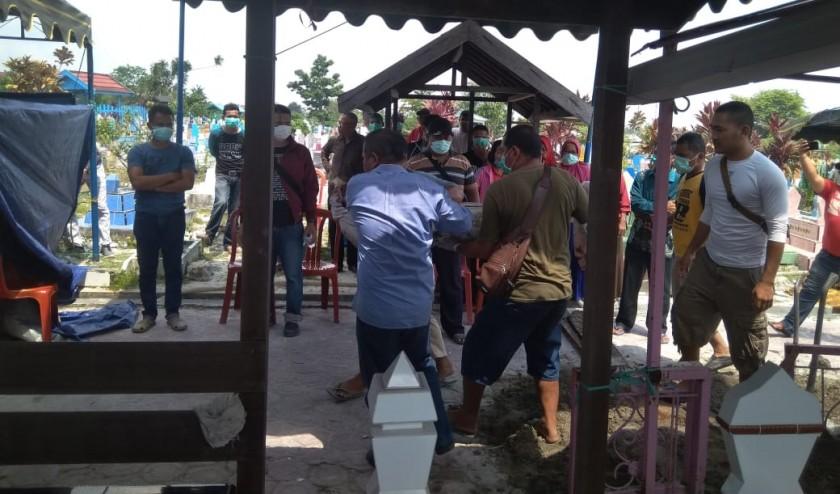 Petugas saat menggali makam kedua nelayan Mendawai guna dilakukan otopsi ulang, Minggu (10/11/2019).