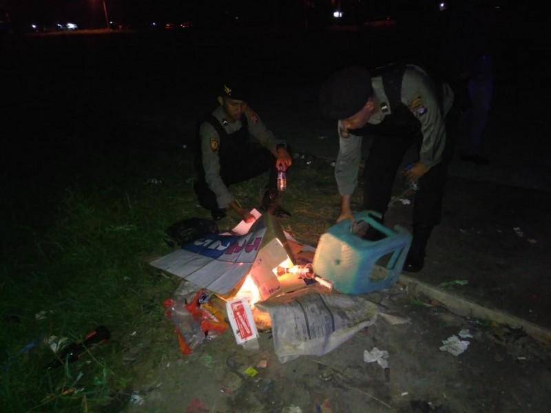 Anggota saat membakar bekas lapak perjudian yang ditinggal kabur para pelakunya Sabtu (16/11/2019) malam.