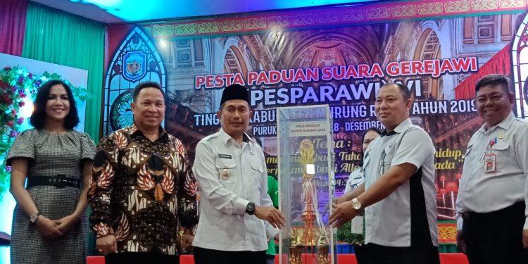 Wabup Rejikinoor saat menyerahkan secara simbolis trophy Pesparawi kepada Camat Murung Banjang Jalin.