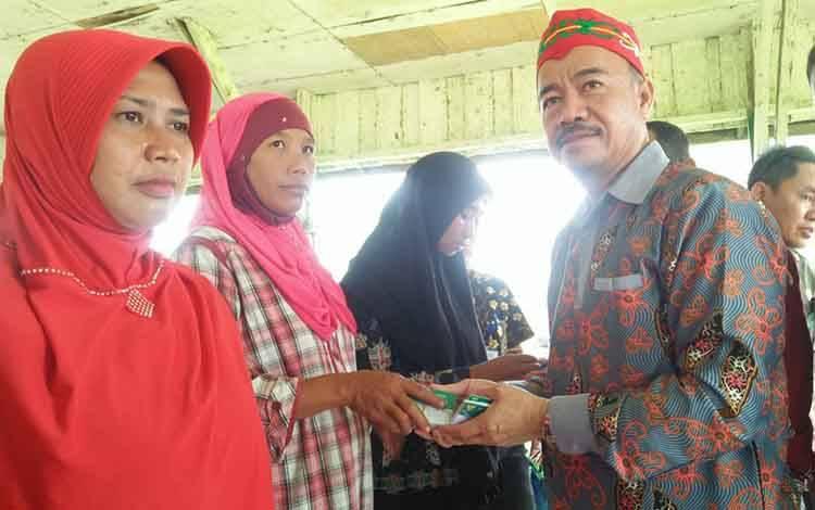 Bupati Seruyan Yulhaidir saat menyerahkan secara simbolis kartu BPJS kepada warga UPT Tanggul Harapan Kamis (30/1).