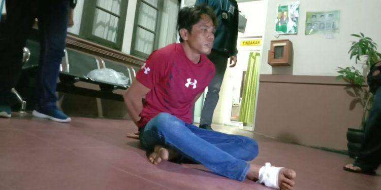 Pelaku saat diamankan dengan kondisi terluka kakinya usai didor polisi Jumat (31/1/2020) malam.
