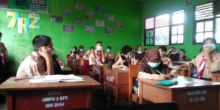 Pelajar SMP saat memakai masker karena tak sanggup mencium bau sampah dari depo yang berada tak jauh dari sekolah Selasa (4/2/2020).