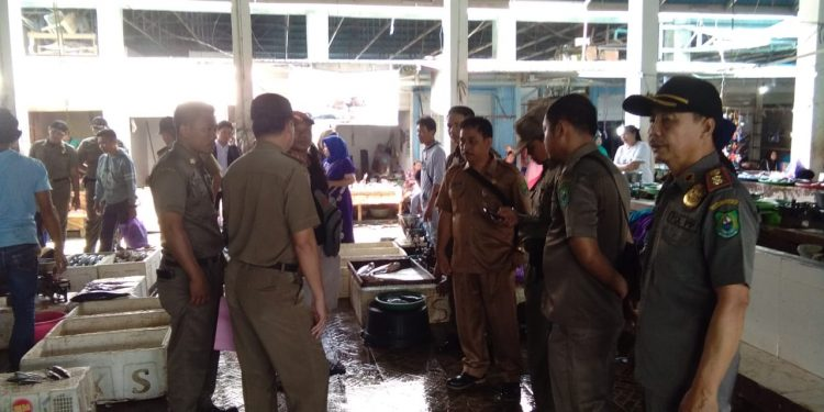 Kasatpol PP dan Damkar Kabupaten Kapuas Syahripin bersama jajarannya saat melakukan pengecekan di lokasi pasar Rabu (12/2).