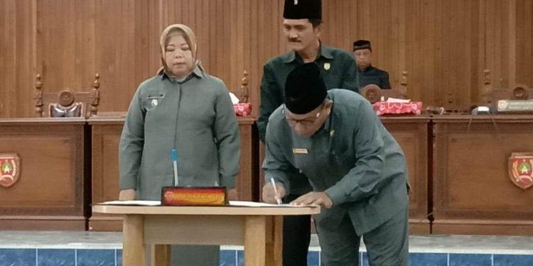 Wakil Ketua II DPRD Kobar Bambang Suherman disaksikan Wakil Ketua I Mulyadin dan Bupati Kobar Hj Nurhidayah saat mengesahkan 4 ranperda menjadi perda Rabu (12/2).