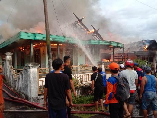 Petugas Damkar Kobar dibantu warga saat melakukan pemadaman api di lokasi kejadian Jumat (14/2/2020).