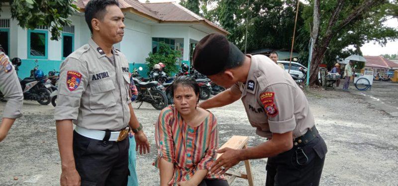 Anggota Polisi saat menenangkan perempuan yang diduga depresi Senin (17/2/2020).