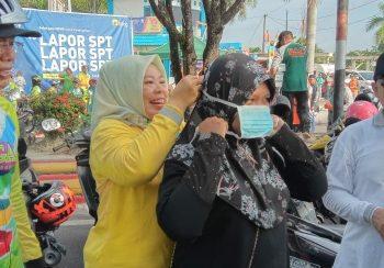 Bupati Kobar Hj Nurhidayah memasang masker kepada warga saar CFD di Bundaran Pancasila, Minggu (8/3). Foto : yusbob