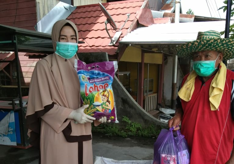 BAGI SEMBAKO --Ketua DPD Lasqi Katingan, Endang Susilawatie, berikan paket sembako kepada padangang sayur keliling. Foto : MI