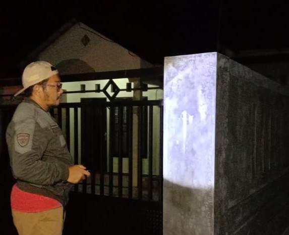 Salah seorang warga saat mengamati bekas coretan di tembok pagar Rabu (22/4) dini hari.