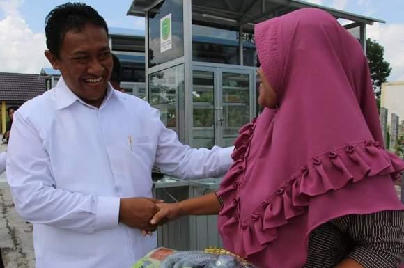 Bupati Pulang Pisau Edy Pratowo saat bersalaman dengan warga seusai menyerahkan bantuan.
