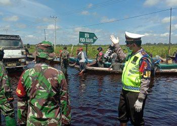 BANJIR - Ruas jalan provinsi arah Palangka Raya-Bukit Rawi kembali ternedam banjir. Tampak anggota PJR Polda Kalteng dan Anggota TNI membantu pengaturan arus lalu lintas, Senin (4/5/2020). Foto : am