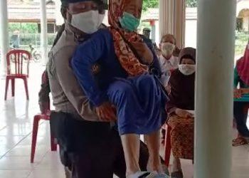Tampak seorang Babinkamtibmas Lada Mandala Jaya Kecamatan Pangkalan Lada, Brigpol Abdul Salam Saurangi, menggendong seorang nenek penerima BLT, Senin (18/5/2020). Foto : Yus