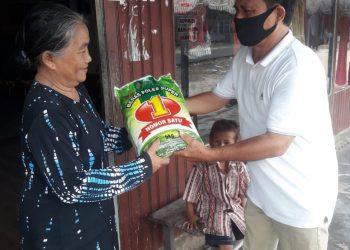 Saat penyerahan bantuan berupa beras kepada warga setempat oleh Legislator Kabupaten Seruyan, Benyamin Pasambe. Foto : Ro