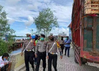 Anggota Satlantas Polres Kobar memantau distribusi sembako dari pelabuhan ke gudang sembako. Foto : yus
