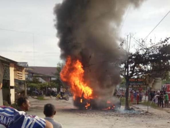 Mobil saat masih terbakar hebat disaksikan warga Sabtu (9/5).