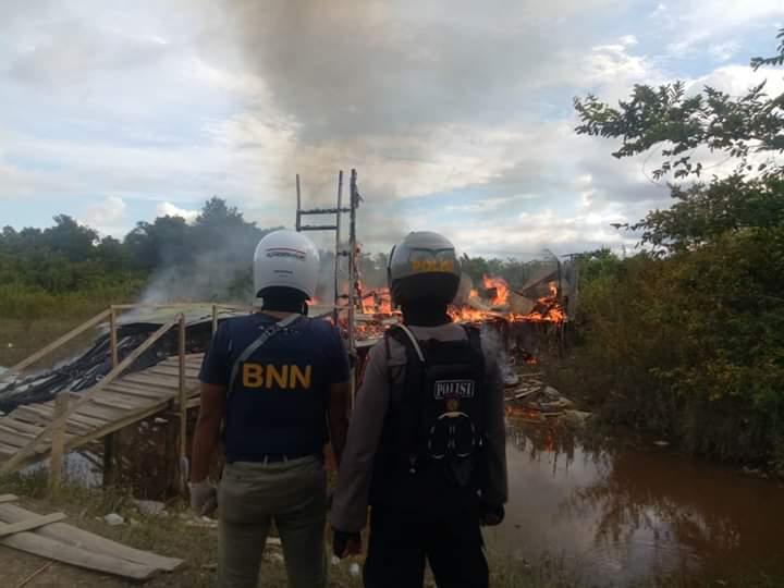 Petugas saat membakar tempat penjualan sabu di kawasan Puntun saat digerebek Jumat (29/5).