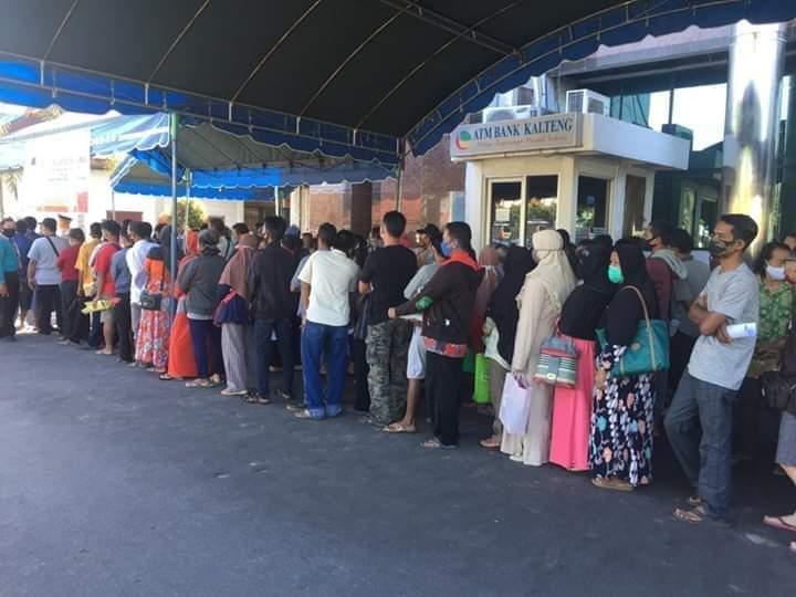 Masyarakat saat mengantre menerima BLT di halaman Bank Kalteng Palangka Raya Minggu (31/5).