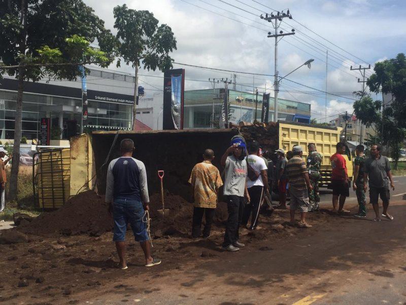 Truk saat terguling dan ditangani warga agar tidak mengganggu jalan Senin (1/6).
